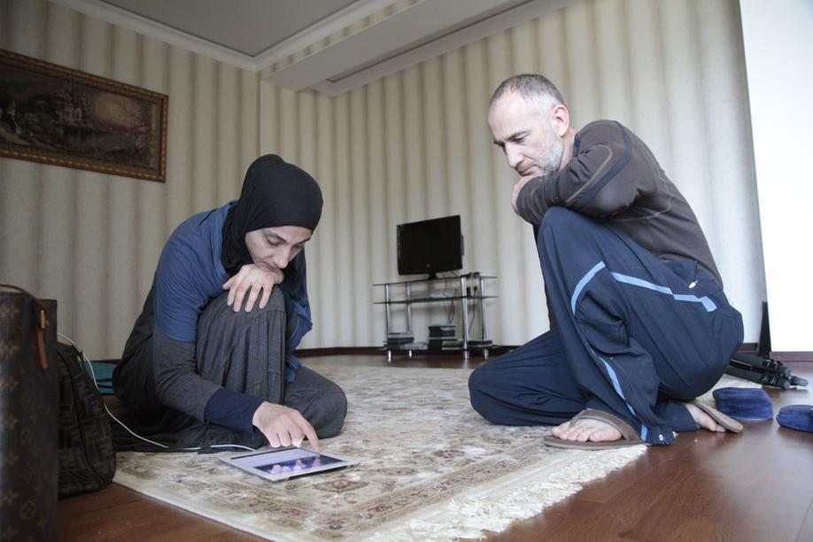 Zubeidat Tsarnaeva, left, and husband Anzor Tsarnaev look at videos on an iPad they say show their sons could not have been involved in the Boston Marathon bombings.